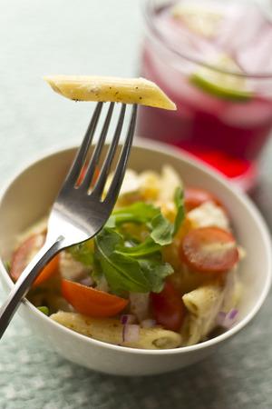 Penne pasta tuna salad with fresh grape tomatoes and arugula photo