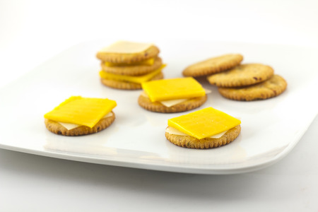 Snack plate of crackers and yellow and white cheddar cheese