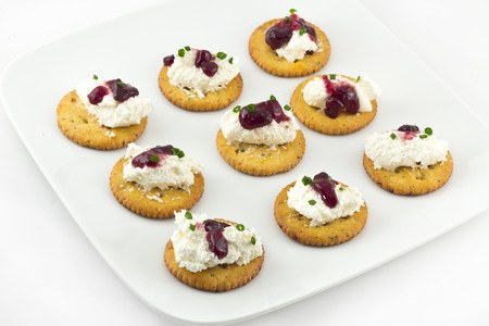 topped: Snack plate of crackers topped with whipped cream cheese and grape Jelly Stock Photo