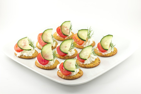 Snack plate of crackers topped with tomato cucumber dill and cheese
