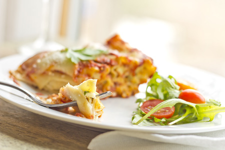 Home made cheese lasagna with arugula salad and a glass of red wine Imagens - 35635642