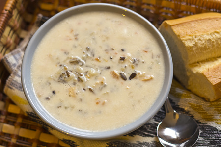 Creamy Chicken and Wild rice soup in a basket with bread for dipping photo