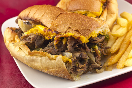 A messy Philly Cheesesteak with onions peppers and mushrooms, fries on the side