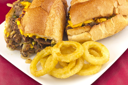 A messy Philly Cheesesteak with onions peppers and mushrooms, onion rings on the side
