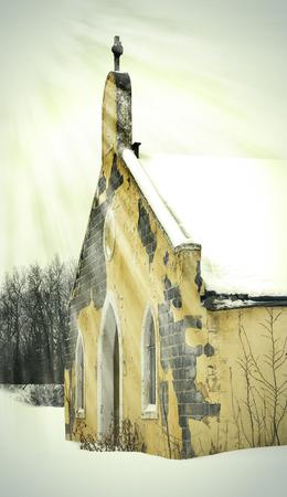 forlorn: Sunbeams on an old abandoned snow covered church building Stock Photo