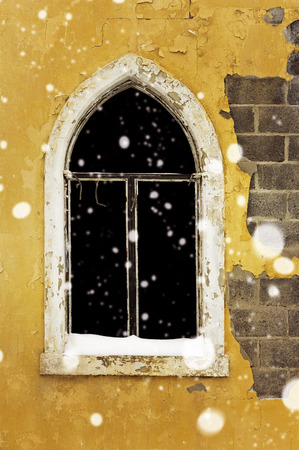 pealing: Gothic window of abandoned building on a snowy day Stock Photo