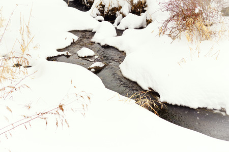 trickles: Stream slowly trickles through the ice and snow of winter