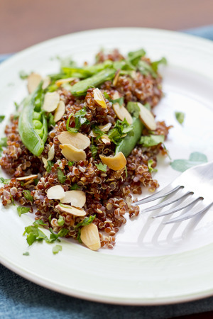 nutty: Healthy nutty red quinoa salad with sugar snap peas sliced toasted almonds and chopped parsley Stock Photo