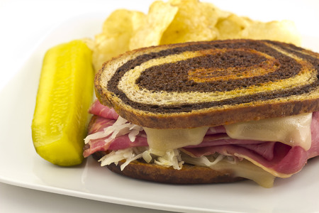 pumpernickel: Famous New York Reuben corned beef sandwich with chips and a pickle