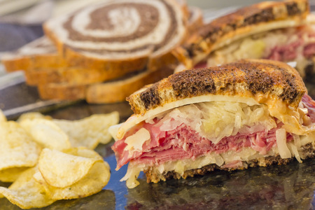 reuben: Famous New York Reuben corned beef sandwich with chips and a pickle