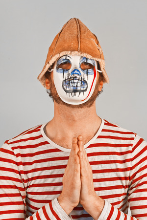 Weird scary masked mime in striped red and white shirt Stock Photo