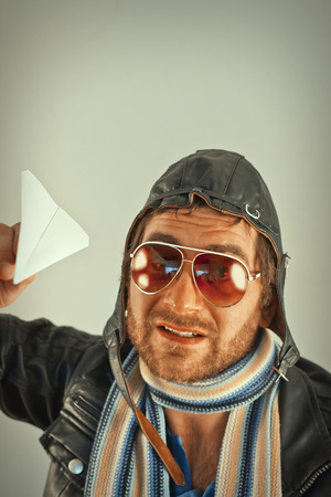 scraggly: Aviator pilot with hat and sunglasses plays with paper planes