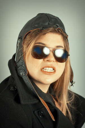 grinding teeth: Female aviator pilot with hat and sunglasses cool portrait