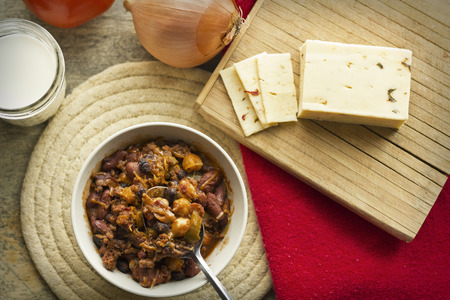 Hot and spicy Chili con carne with a glass of milk and pepper jack cheese