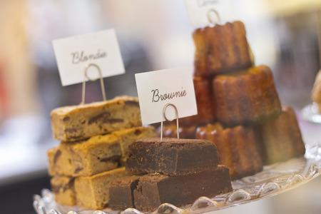display case: Display case of fresh brownies and blondies and dessert cakes