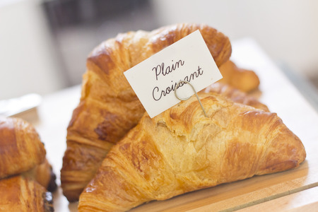 display case: Tasty flaky plain croissants in bakery display case