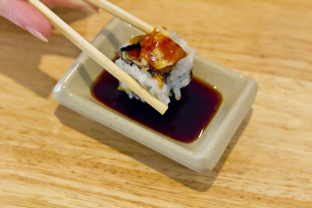 soysauce: Single piece of sweet potato sushi being dipped in soy sauce