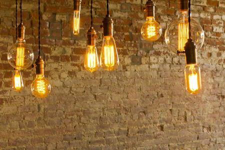 Decorative antique edison style light bulbs against brick wall background