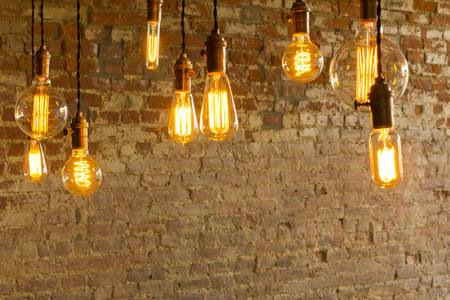 Decorative antique edison style light bulbs against brick wall background Imagens - 37347813