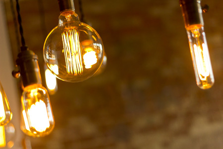 brick: Decorative antique edison style light bulbs against brick wall background