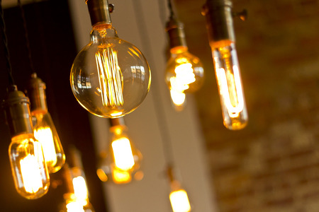 background lights: Decorative antique edison style light bulbs against brick wall background