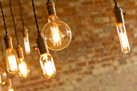incandescent: Decorative antique edison style light bulbs against brick wall background