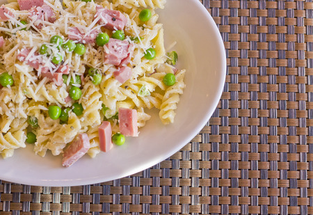 rotini: Pasta salad with ham and green peas topped with shredded parmesan Stock Photo