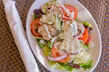 Vegetarian salad with ranch dressing with fresh mushrooms tomatoes cucumbers red onion and parmesan cheese