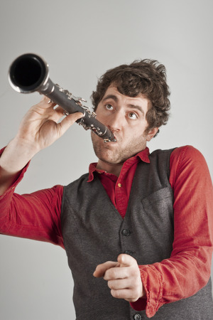 red handed: Silly man plays clarinet one handed while pointing at the audience