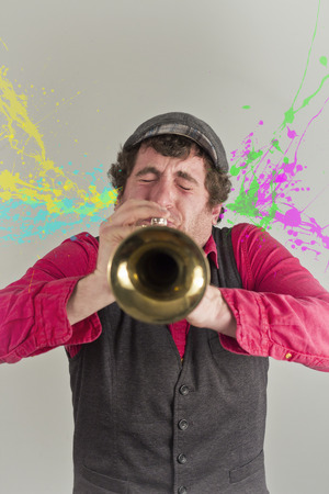 erupt: Paint splatters erupt out of this horn players ears as he tries to hit a high note Stock Photo