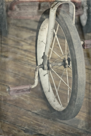 antique tricycle: Antique red tricycle in vintage inspired desaturated film style photograph