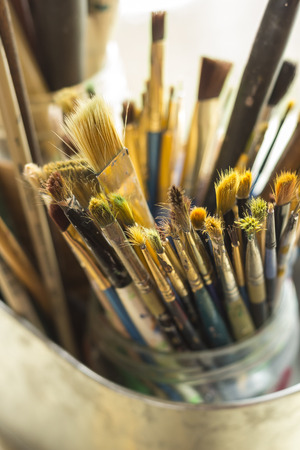 Container kit of assorted and stained old artist paintbrushes