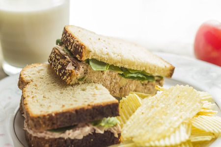 Tuna salad sandwich with ripple potato chips and a glass of milk