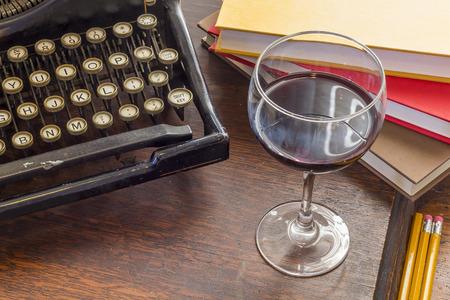 maquina de escribir: Máquina de escribir vieja de la vendimia con un vaso de vino lápices y libros en esta escritura creativa retro y relazation temática escritorio de la tapa