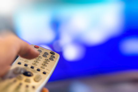 changing channels: Close up of remote in hand with shallow depth of field during television watching Stock Photo