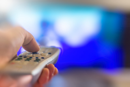 flat screen television: Close up of remote in hand with shallow depth of field during television watching Stock Photo
