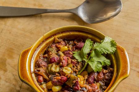 Hot and spicy chili con carne served in a cute mini pot with cilantro garnish photo