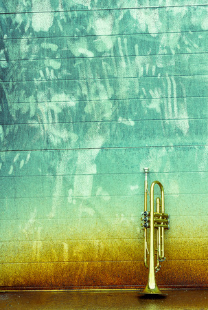 Old worn trumpet stands alone against a grungy wall outside a jazz club