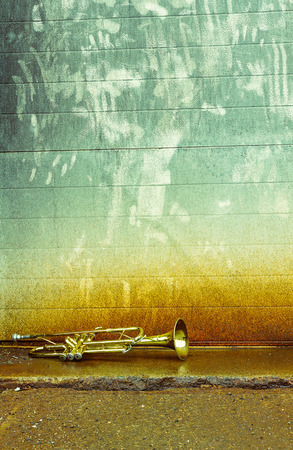 pealing: Old worn trumpet stands alone against a grungy wall outside a jazz club