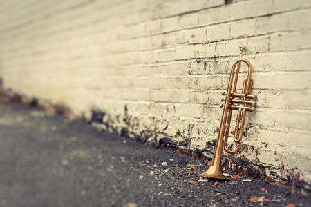 Oude versleten trompet staat alleen tegen een grungy pellen witte bakstenen muur buiten een jazzclub