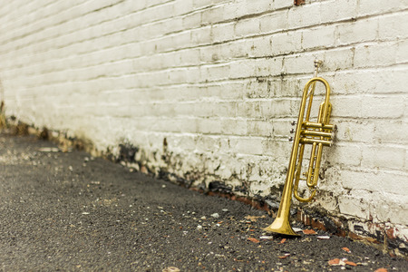 pealing: Old worn trumpet stands alone against a grungy pealing white brick wall outside a jazz club Stock Photo