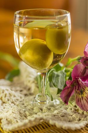 fleurs des champs: Douce japonaise vin de prune avec des fruits dans le verre avec de belles fleurs sauvages photographi� roses Banque d'images