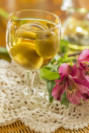 frill: Sweet Japanese plum wine with fruit in glass photographed with beautiful pink wildflowers