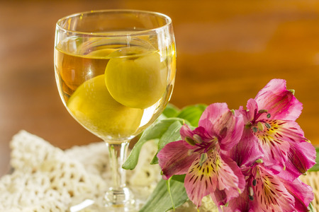 ume: Sweet Japanese plum wine with fruit in glass photographed with beautiful pink wildflowers