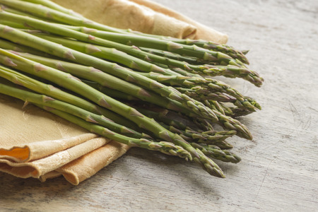 Fresh organic asparagus straight from the farmers market on distressed table top Stock Photo