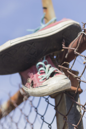 rusty chain: Pair of old worn classic sneakers hang from rusty chain link fence Stock Photo