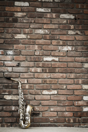 leans: Lone old saxophone leans against brick wall outside abandoned jazz club Stock Photo