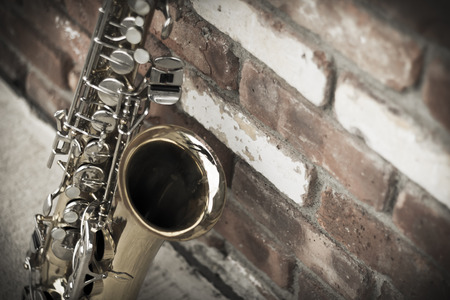 Lone old saxophone leans against brick wall outside abandoned jazz club Banque d'images