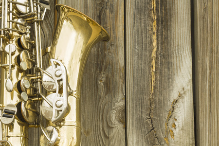 saxof�n: Lone saxof�n de edad se inclina contra la cerca de madera fuera de un club de jazz