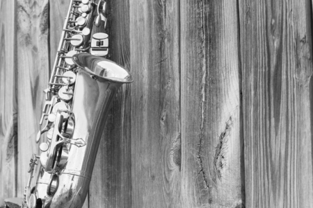 saxofón: Lone saxofón de edad se inclina contra la cerca de madera fuera de un club de jazz
